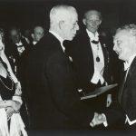 A képen a díjátadás pillanata látható. V. Gusztáv svéd király átnyújtja Szent-Györgyi Albertnek a díjat jelképező Nobel-érmet és Nobel-diplomát